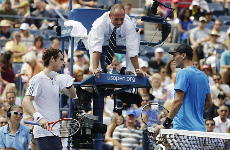 Photo -   Britain's Andy Murray, left, and Czech Republic's Tomas Berdych, right, talk with the umpire about a call during a semifinal match at the 2012 US Open tennis tournament, Saturday, Sept. 8, 2012, in New York. (AP Photo/Darron Cummings)