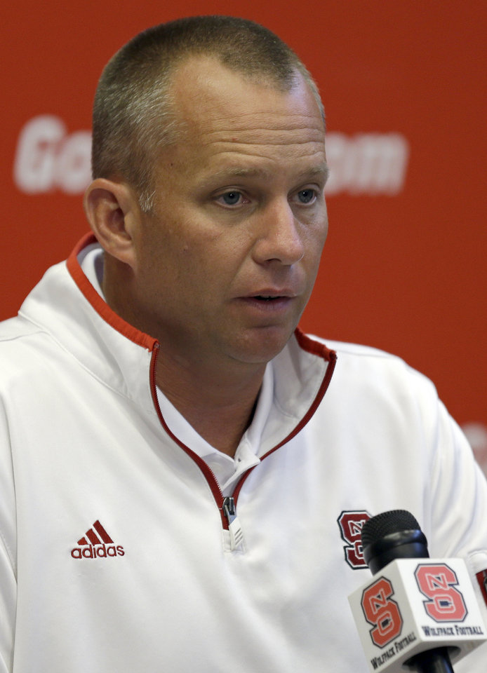 Photo - North Carolina State coach Dave Doeren speaks with reporters during an NCAA football media day in Raleigh, N.C., Sunday, Aug. 10, 2014. (AP Photo/Gerry Broome)