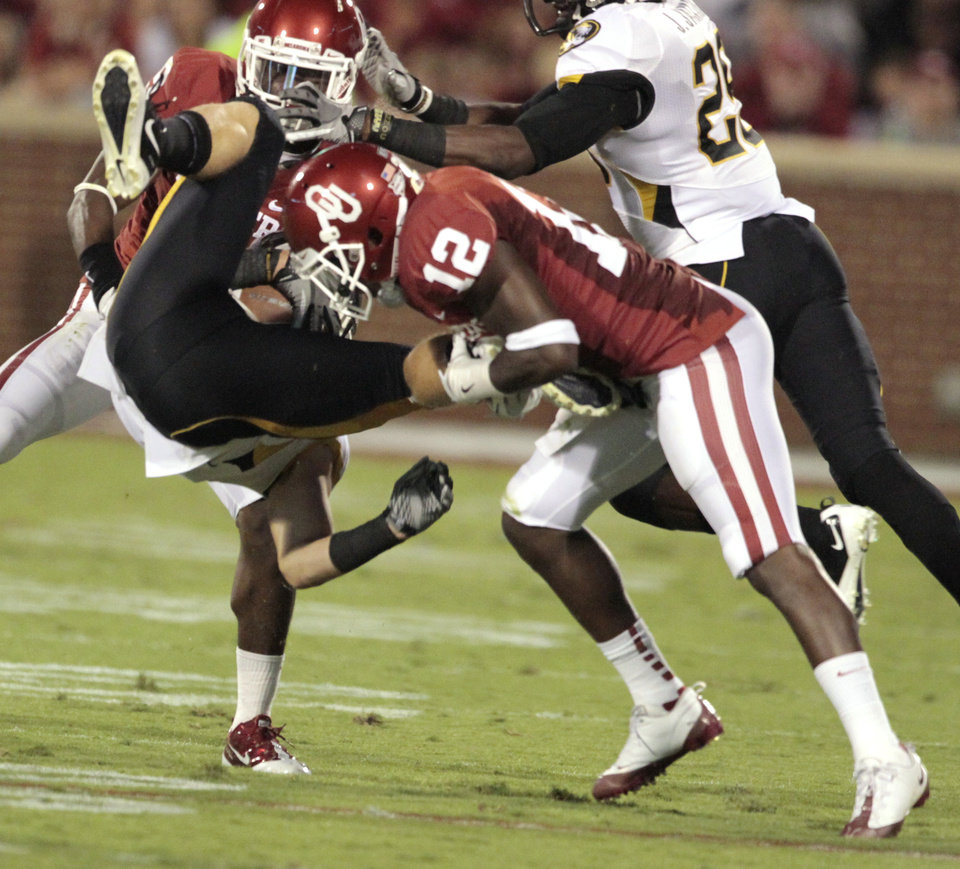 Photo - Missouri's T.J. Moe (28) is upended by Oklahoma's Javon Harris (12) during the college football game between the University of Oklahoma Sooners (OU) and the University of Missouri Tigers (MU) at the Gaylord Family-Memorial Stadium on Saturday, Sept. 24, 2011, in Norman, Okla. Photo by Steve Sisney, The Oklahoman