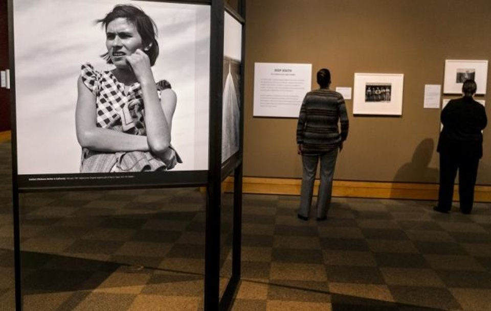 Photo -  People look at images in the exhibit