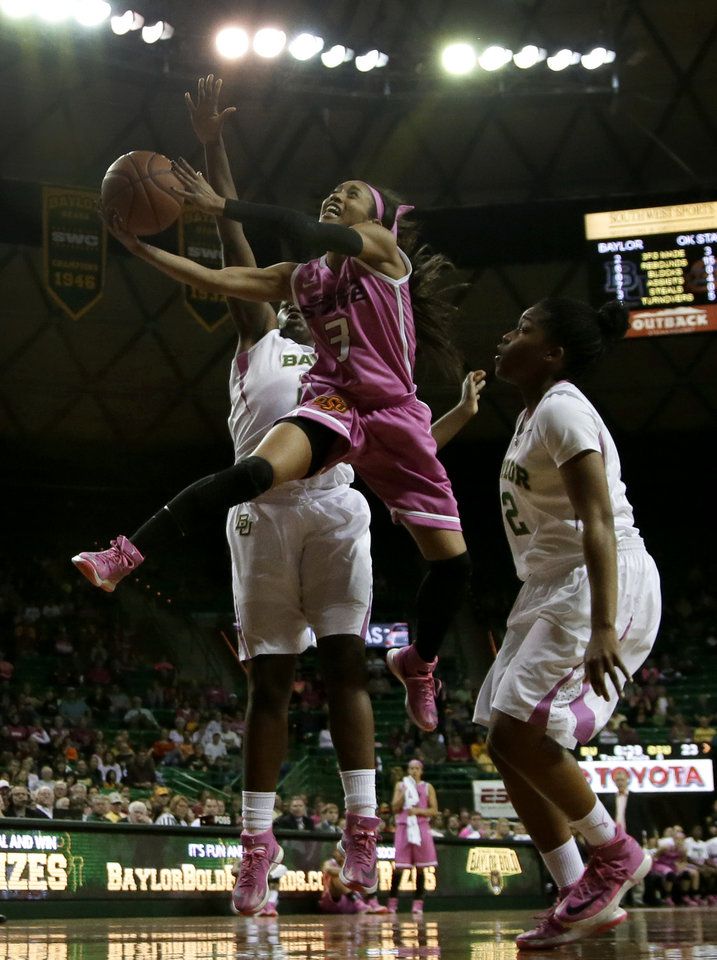 Photo - Oklahoma State 's Tiffany Bias (3) goes up to shoot between Baylor defenders Sune Agbuke, left, and Niya Johnson, right, in the first half of an NCAA college basketball game on Sunday, Feb. 9, 2014, in Waco, Texas. Both teams wore uniforms accented with pink for breast cancer awareness. (AP Photo/Tony Gutierrez)