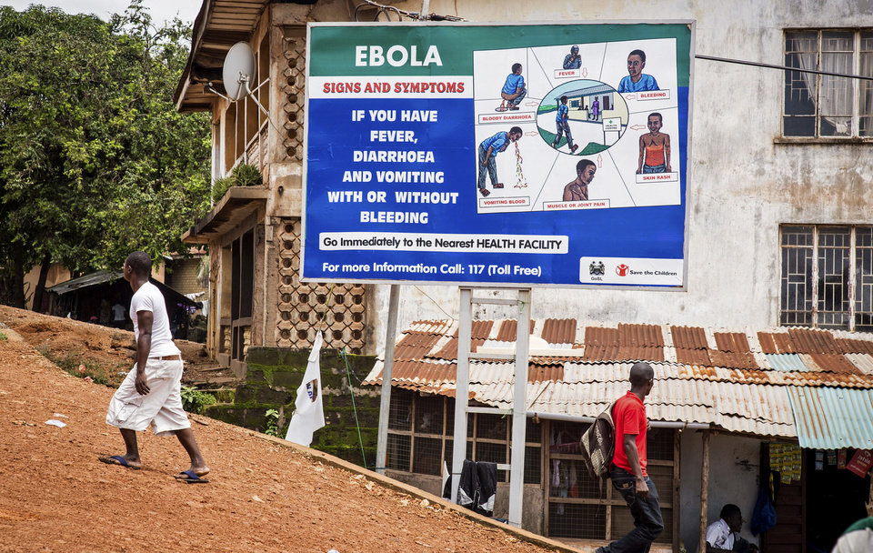 Photo - People walk past a billboard encouraging people suffering from symptoms linked to Ebola to present themselves at a health facility for treatment in Freetown, Sierra Leone, Thursday,  Aug. 7, 2014. While the Ebola virus outbreak has now reached four countries, Liberia and Sierra Leone account for more than 60 percent of the deaths, according to the World Health Organization. The outbreak that emerged in March has claimed at least 932 lives. (AP Photo/ Michael Duff)