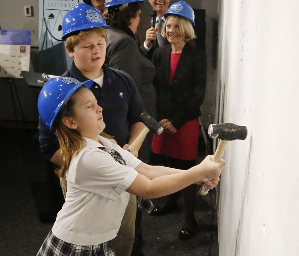 Photo - Caroline Watkins, 10, and her brother Ford Watkins, 11, take turns hitting a wall during a wall breaking ceremony at the Oklahoma City National Memorial & Museum in Oklahoma City. Caroline and Ford's mother is Kari Watkins, executive director of the Oklahoma City National Memorial & Museum.  Steve Gooch - The Oklahoman