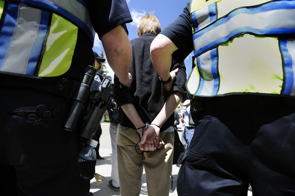 Photo -   University of Colorado senior John Demopoulos is detained by police after trespassing on the Norlin Quad on the University of Colorado campus in Boulder, Colo., on Friday, April 20, 2012. A block-long line of protesters marched onto the University of Colorado, testing the school's determination to push the annual April 20 marijuana celebration off campus. (AP Photo/The Daily Camera, Jeremy Papasso)