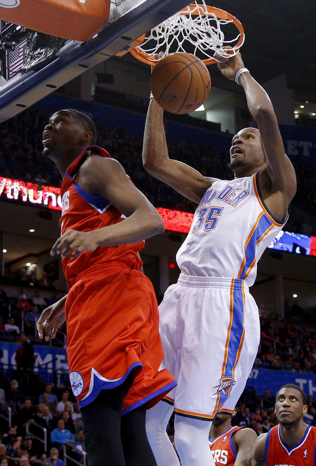 Photo - Oklahoma City's Kevin Durant (35) dunks beside Philadelphia's Jarvis Varnado (40) during an NBA basketball game between the Oklahoma City Thunder and the Philadelphia 76ers at Chesapeake Energy Arena in Oklahoma City, Tuesday, March 4, 2014. Photo by Bryan Terry, The Oklahoman