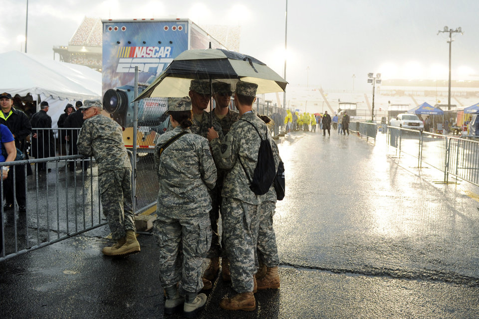 Photo -   Members of the Virginia National Guard huddle under an umbrella as they wait for the start of the NASCAR Sprint Cup Series auto race at Richmond International Raceway in Richmond, Va., Saturday, Sept. 8, 2012. (AP Photo/Clem Britt)