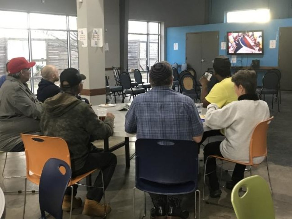Photo -  Residents of the Homeless Alliance's WestTown apartments watch Super Bowl LIV with volunteers from Chabad Community Center for Jewish Life and Learning during Chabad's Super Soul Party at the Homeless Alliance's day shelter, 1724 NW 4 [Carla Hinton/The Oklahoman]
