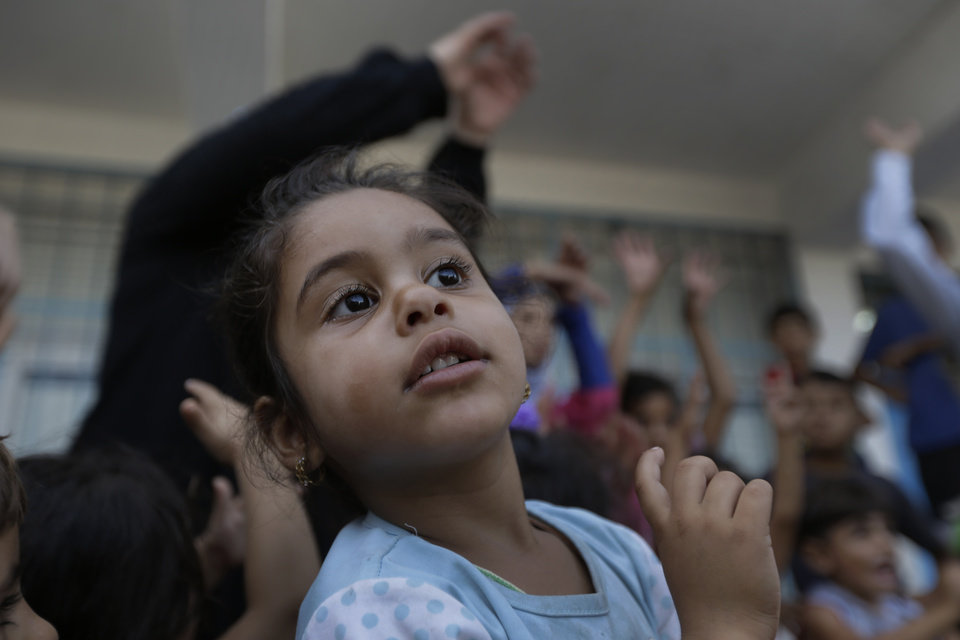 Photo - Displaced Palestinian Gazal Ahmed Sehda, 5, participates in a play session with other children, at a U.N. school where they had sought refuge along with their families during the war, in Gaza City, Gaza Strip, Thursday, Aug. 7, 2014. Taking advantage of the continuing ceasefire, volunteers from the local non-profit NGO 'Tomooh' (Ambition), arranged a special play session for children to try and lessen the stress they've been enduring after the weeks of conflict. In the playground the children got a chance to sing and play group games under the caring eye of volunteers. They hope that their efforts will lessen the damage of the traumatic recent weeks events, or at least help them forget for a short while. (AP Photo/Lefteris Pitarakis)