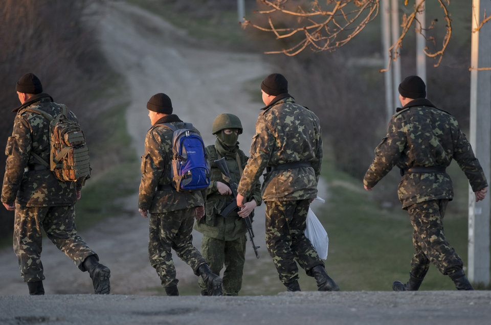 Photo - Ukrainian soldiers walk by a pro-Russian soldier in Perevalne, Ukraine, Saturday, March 15, 2014. Tensions are high in the Black Sea peninsula of Crimea, where a referendum is to be held Sunday on whether to split off from Ukraine and seek annexation by Russia. (AP Photo/Vadim Ghirda)