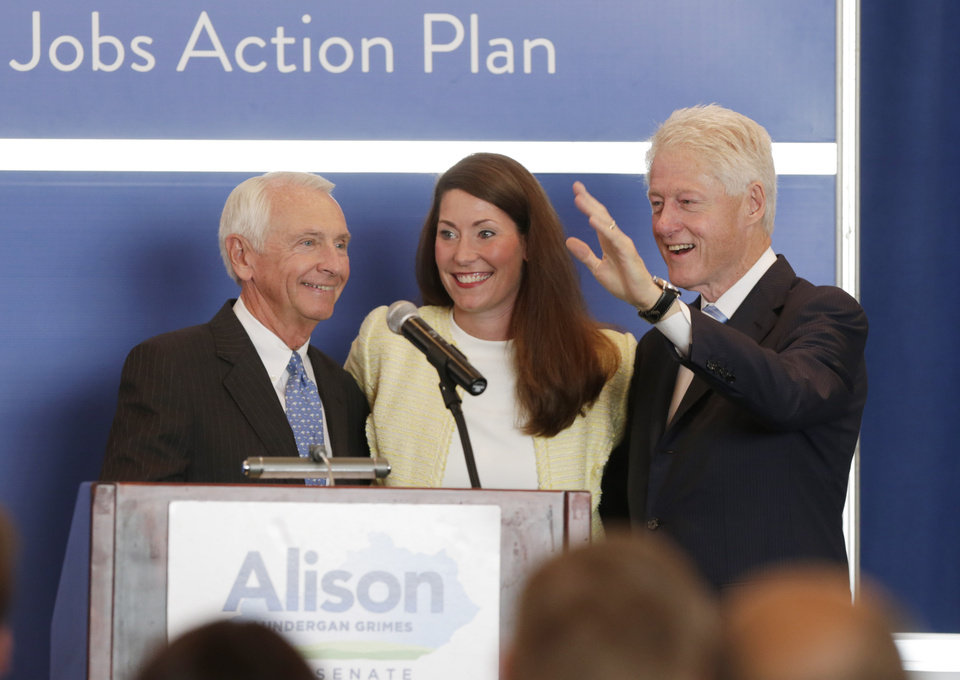 Photo - Gov. Steve Beshear, left welcomes  Alison Lundergan Grimes and former President Bill Clinton to the stage during a campaign event for Grimes at the Carrick House in Lexington, Ky., Wednesday, Aug. 6, 2014. Grimes is the Democratic challenger to Sen. Mitch McConnell.  (AP Photo/The Herald-Leader, Pablo Alcala)