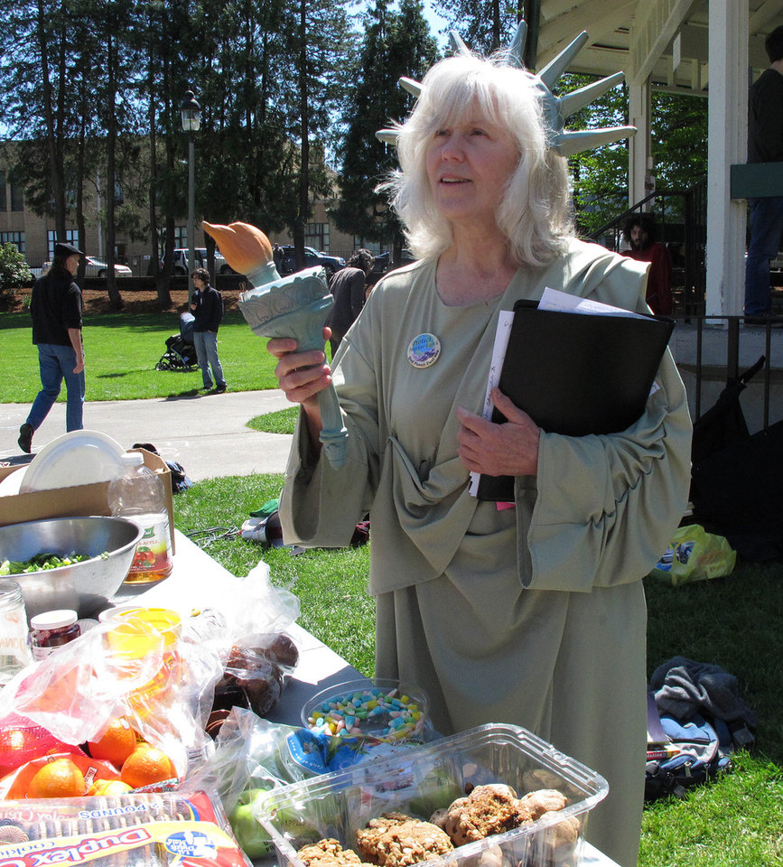 Mary Hath Spokane of Rainier, Wash., waits at a food table at Sylvester Park while dressed as the Statue of Liberty, during a May Day festival Wednesday, May 1, 2013, in Olympia, Wash. About 100 people took part in the event. (AP Photo/Rachel La Corte)