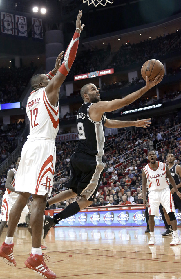 Photo - San Antonio Spurs' Tony Parker (9) goes to the basket against Houston Rockets' Dwight Howard (12) as Aaron Brooks (0) watches during the second half of an NBA basketball game Tuesday, Jan. 28, 2014, in Houston. The Rockets won 97-90. (AP Photo/Pat Sullivan)