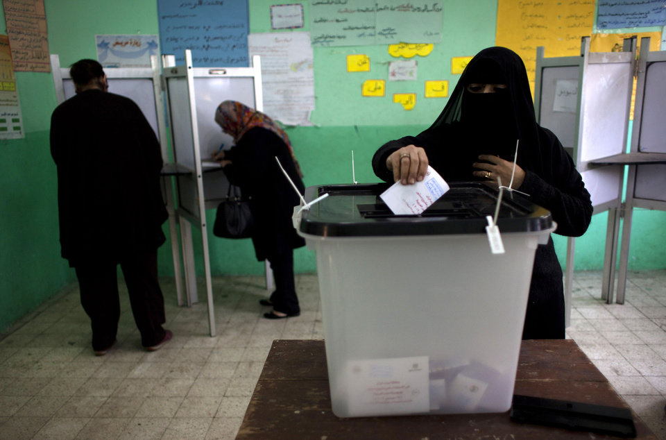 A veiled Egyptian woman casts her vote at a polling station in the second round of a referendum on a disputed constitution drafted by Islamist supporters of president Mohammed Morsi, in Giza, Egypt, Saturday, Dec. 22, 2012. (AP Photo/Nasser Nasser)