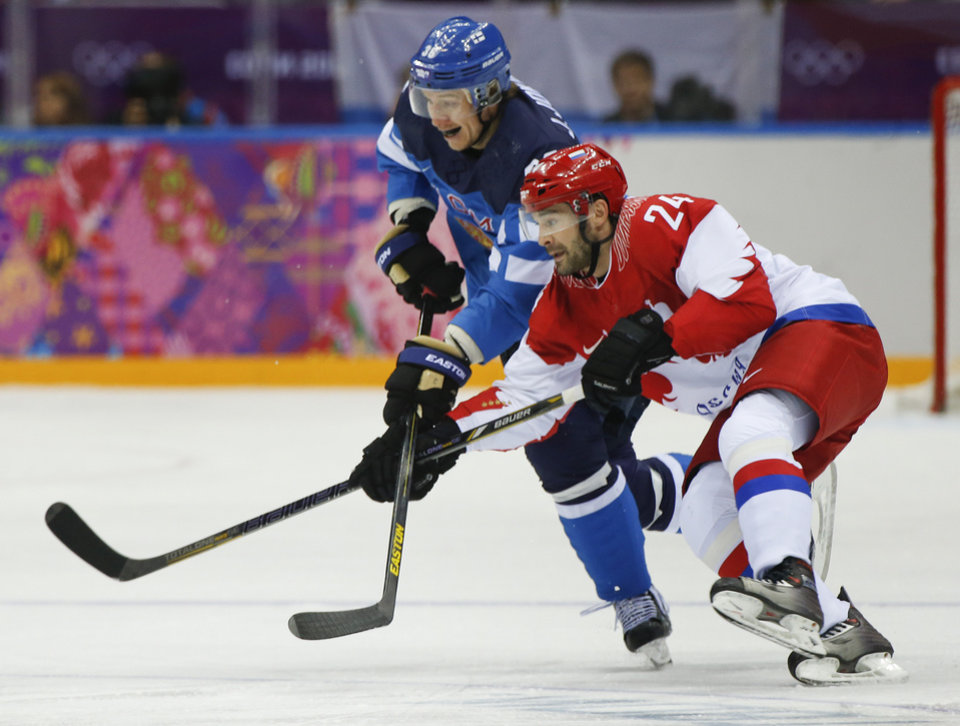 Photo - Russia forward Alexander Popov races after the puck against Finland forward Jussi Jokinen during the first period of a men's quarterfinal ice hockey game at the 2014 Winter Olympics, Wednesday, Feb. 19, 2014, in Sochi, Russia. (AP Photo/Julio Cortez)