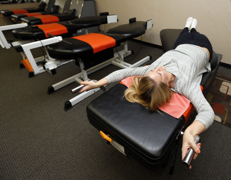 Photo - Chelsey Edmondson uses a robotic exercise machine at Tan & Tone Unlimited in Stillwater. Edmondson is a new employee at the salon and was trying the machine for the first time as part of her training.  NATE BILLINGS - THE OKLAHOMAN