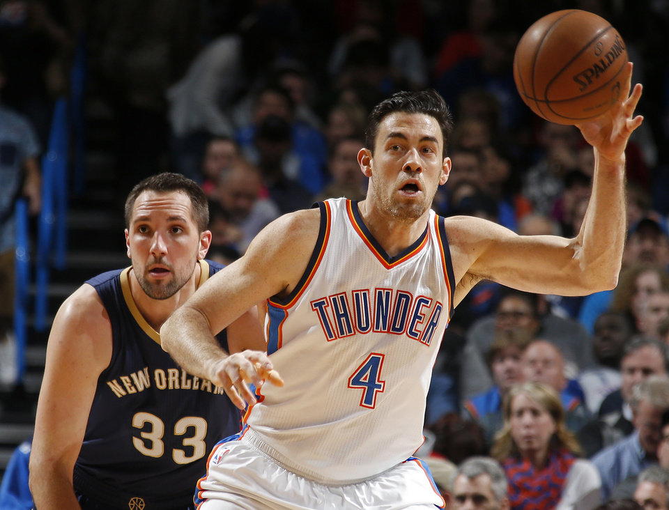 Photo - Oklahoma City's Nick Collison (4) gathers the ball in front of New Orleans' Ryan Anderson (33) during an NBA game between the Oklahoma City Thunder and the New Orleans Pelicans at Chesapeake Energy Arena on Friday, Feb. 6, 2015. Photo by Bryan Terry, The Oklahoman