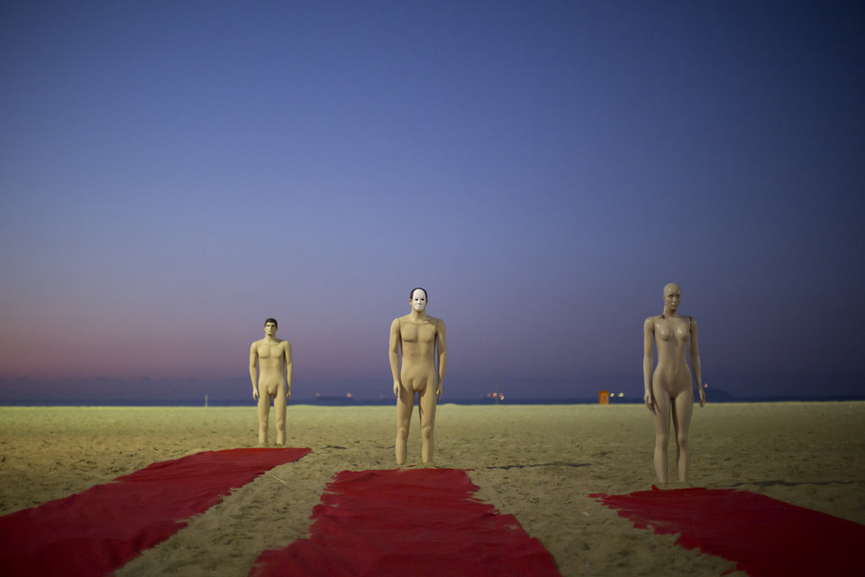 Photo - A trio of mannequins stand upright on the sands of Copacabana beach, placed there by Rio de Paz activists as part of a protest staged to press for clarifications on missing persons including a bricklayer who recently disappeared, in Rio de Janeiro, Brazil, Wednesday, July 31, 2013. The 42-year-old father of six was picked up for police questioning on suspicions of involvement in drug trafficking, but was released shortly thereafter. He has not been seen since. The Rio de Paz civic organization cites official statistics showing that nearly 35,000 people were reported as missing in Rio state alone over the past five years. (AP Photo/Felipe Dana)