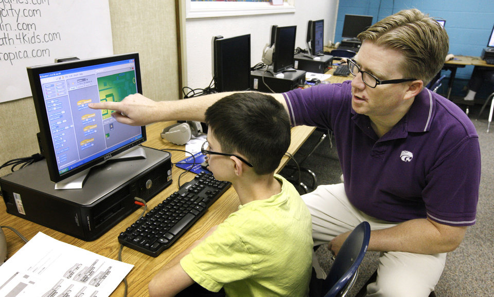 Photo - Instructor Wesley Fryer helps Treven Roach, 10, a fourth-grader at Independence Elementary, to write computer code during spring break at Yukon Public Schools' Scratch Camp.