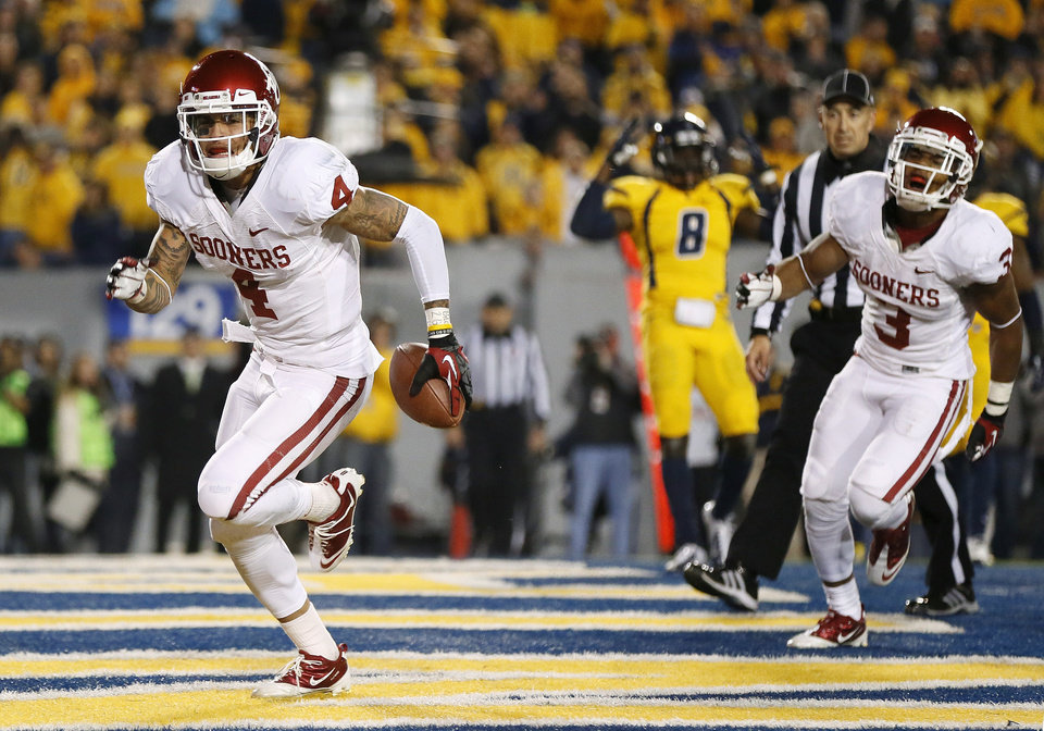 Photo - Oklahoma's Kenny Stills (4) runs to the back of the end zone after getting up from scoring the game-winning touchdown in the final minute of a college football game between the University of Oklahoma and West Virginia University on Mountaineer Field at Milan Puskar Stadium in Morgantown, W. Va., Nov. 17, 2012. Celebrating at right is Oklahoma's Sterling Shepard (3). OU won, 50-49. Photo by Nate Billings, The Oklahoman