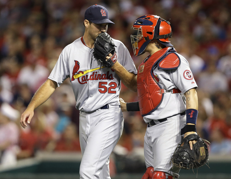 Photo - St. Louis Cardinals starting pitcher Michael Wacha (52) talks with catcher Yadier Molina in the fifth inning of a baseball game against the Cincinnati Reds, Tuesday, Sept. 3, 2013, in Cincinnati. (AP Photo/Al Behrman)
