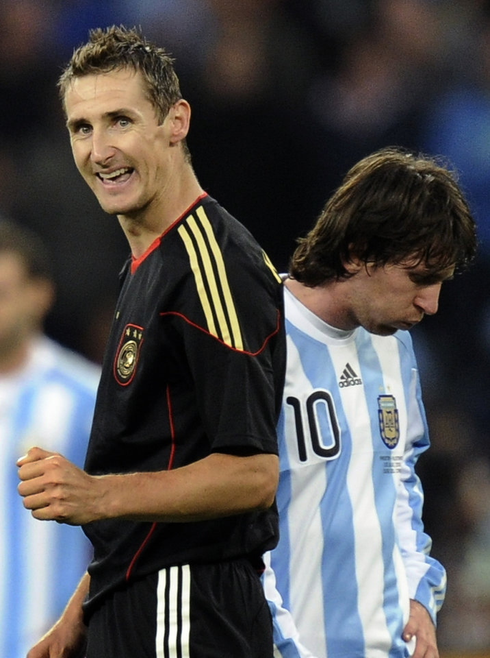 Photo - FILE - The July 3, 2010 file photo shows Germany's Miroslav Klose, left, walking past Argentina's Lionel Messi as he celebrates after scoring his team's fourth goal during the World Cup quarterfinal soccer match between Argentina and Germany at the Green Point stadium in Cape Town, South Africa. Germany won 4-0. On Sunday, July 13, 2014, Germany and Argentina will face each other again in the final of the 2014 soccer World Cup. (AP Photo/Martin Meissner, file)