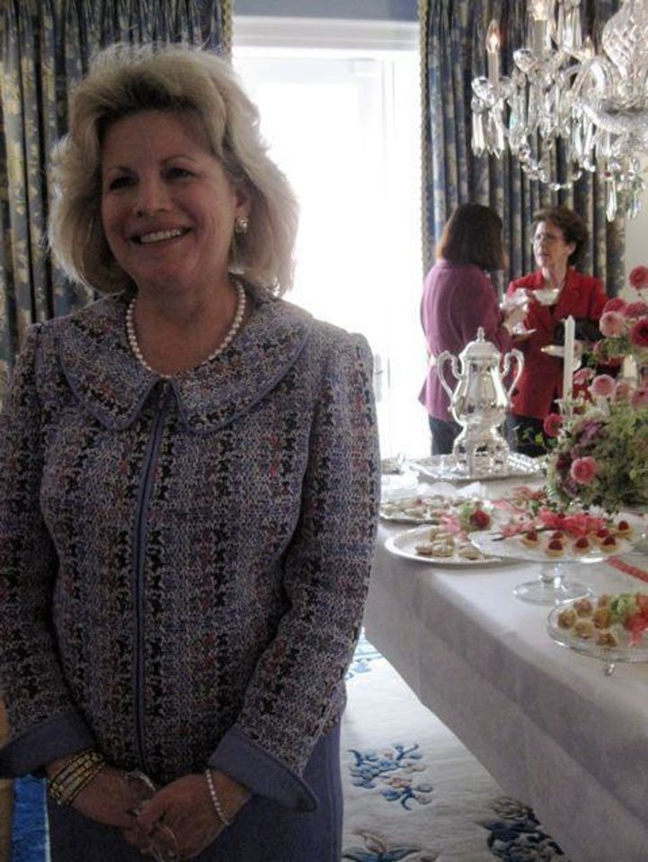 HEARTS AND LOTS OF FLOWERS...Party planner extraordinaire Debby Dudman shows the beautiful tea table. (Photo by Helen Ford Wallace).