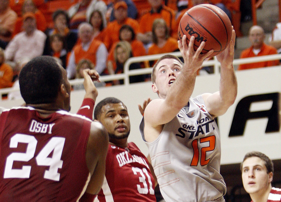 Photo - OSU's Keiton Page (12) takes a shot near OU's Romero Osby (24), Barry Honore (31) and Tyler Neal (15) in the second half during the Bedlam men's college basketball game between the Oklahoma State University Cowboys and the University of Oklahoma Sooners at Gallagher-Iba Arena in Stillwater, Okla., Monday, Jan. 9, 2012. OSU beat OU, 72-65. Photo by Nate Billings, The Oklahoman