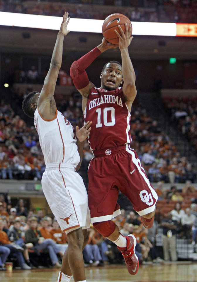 Photo - Oklahoma guard Jordan Woodard (10) looks to pass against Texas guard Isaiah Taylor during the second half of an NCAA college basketball game Saturday, Jan. 4, 2014, in Austin, Texas. Oklahoma won 88-85. (AP Photo/Michael Thomas)