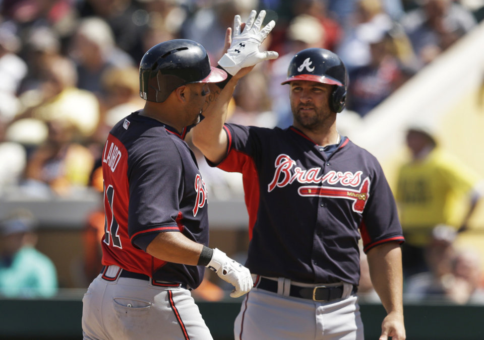 Photo - Atlanta Braves' Gerald Laird, left, is congratulated by teammate Dan Uggla after they both scored on Laird's two-run home run during the sixth inning of a spring exhibition baseball game against the Detroit Tigers in Lakeland, Fla., Tuesday, March 25, 2014. (AP Photo/Carlos Osorio)