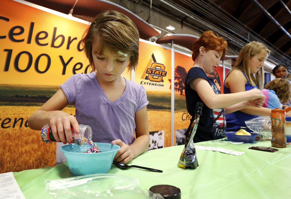 Photo -  Felicity Vanoy, 10, of Oklahoma City, pours colored sprinkles onto her bowl of ice cream in the sundae contest at the Oklahoma County Free Fair. Events also included a saucy salsa contest, ice cream freeze-off, kiddy tractor pull and livestock shows. Photo by Jim Beckel, The Oklahoman   Jim Beckel -