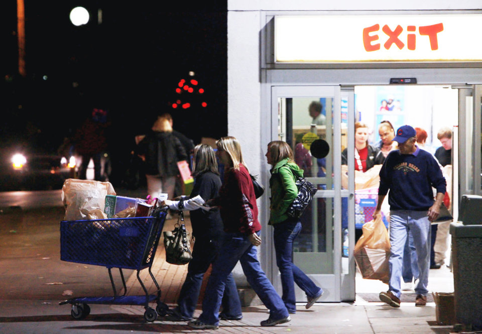 Photo - Customers leave Toys R Us on Friday after bargain shopping early in Tulsa.  PHOTO BY JAMES GIBBARD, TULSA WORLD