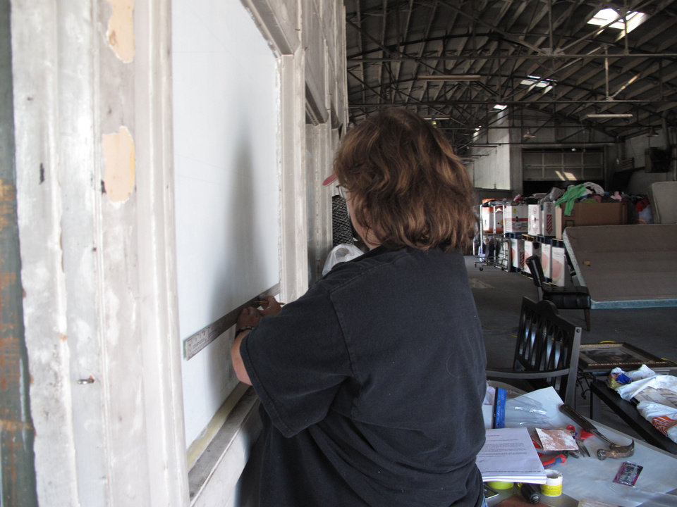 Debbie Richardson, a graphic artist and Velma Police officer, prepares to paint the Jesus House logo on prayer room window at the Oklahoma City shelter. CARLA HINTON - CARLA HINTON