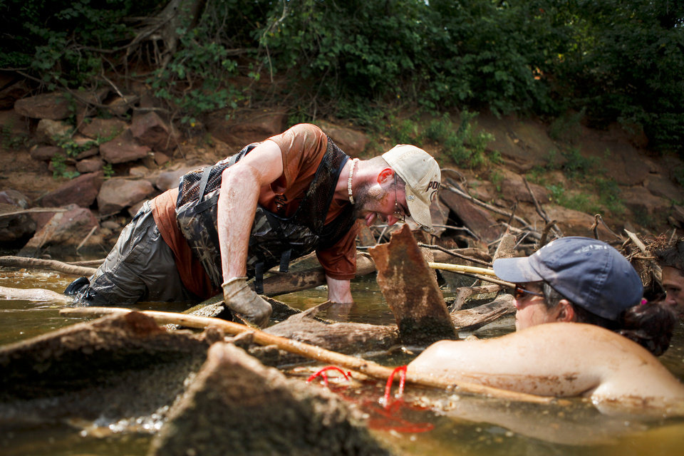 Noodlers Chris Pulchy and Rita Sanders search for flathead catfish on the Cimarron River near Stillwater. Among the new laws set to go into effect is one that will expand the list of fish that noodlers are permitted to catch. Photo by <strong>ZACH GRAY</strong>