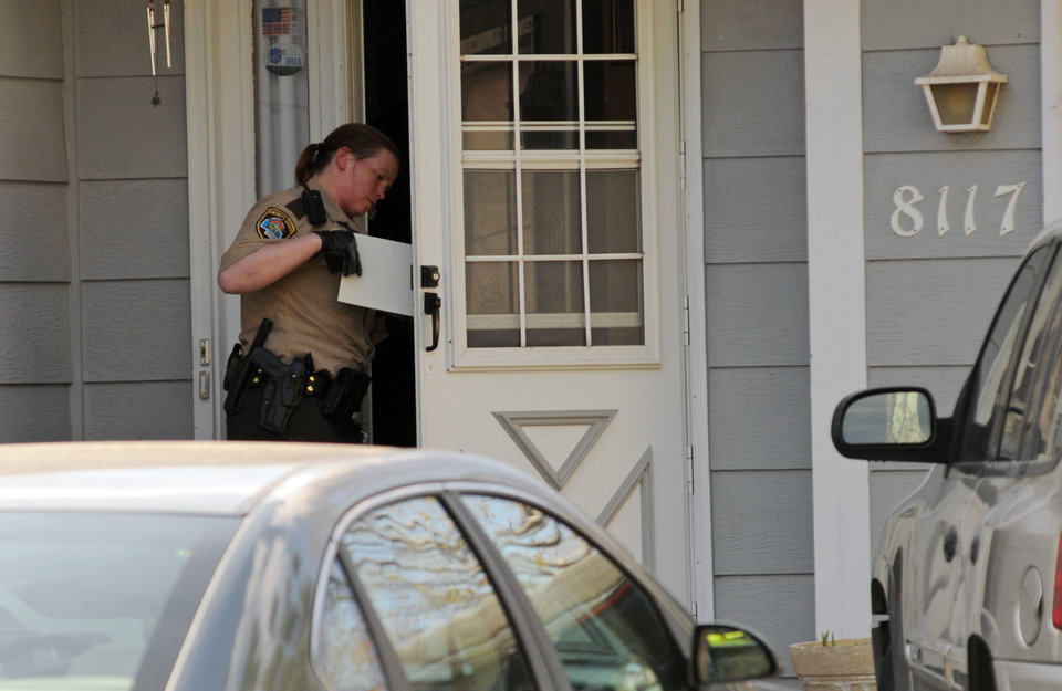 Photo -   A police officer investigates the scene where three people were shot and killed at an in-home day care in Brooklyn Park, Minn., on Monday, April 9, 2012. No arrests were immediately made. (AP Photo/The Star Tribune, Richard Sennott) MANDATORY CREDIT; ST. PAUL PIONEER PRESS OUT; MAGS OUT; TWIN CITIES TV OUT