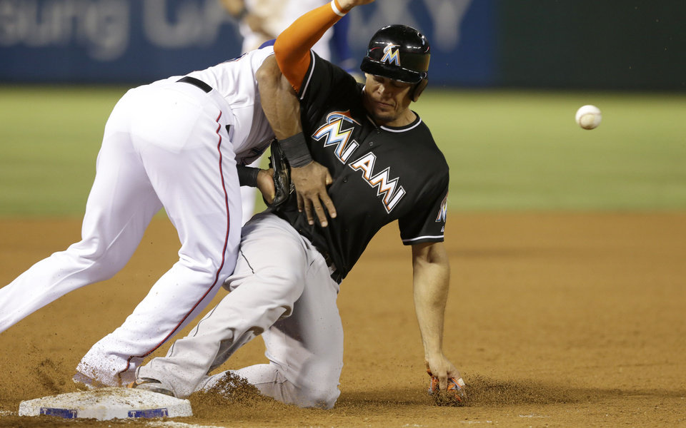 Photo - Miami Marlins Giancarlo Stanton, right, slides safely into third base against Texas Rangers third baseman Adrian Beltre (29) during the eighth inning of a baseball game in Arlington, Texas, Tuesday, June 10, 2014. Stanton reached base on a single by teammate Casey McGehee. (AP Photo/LM Otero)