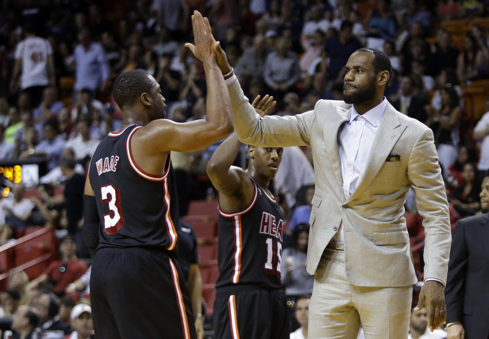 Photo - Miami Heat's LeBron James, right, high-fives Dwyane Wade (3) during a time out in the second half of an NBA basketball game against the Chicago Bulls, Sunday, Feb. 23, 2014, in Miami. The Heat defeated the Bulls 93-79. (AP Photo/Lynne Sladky)