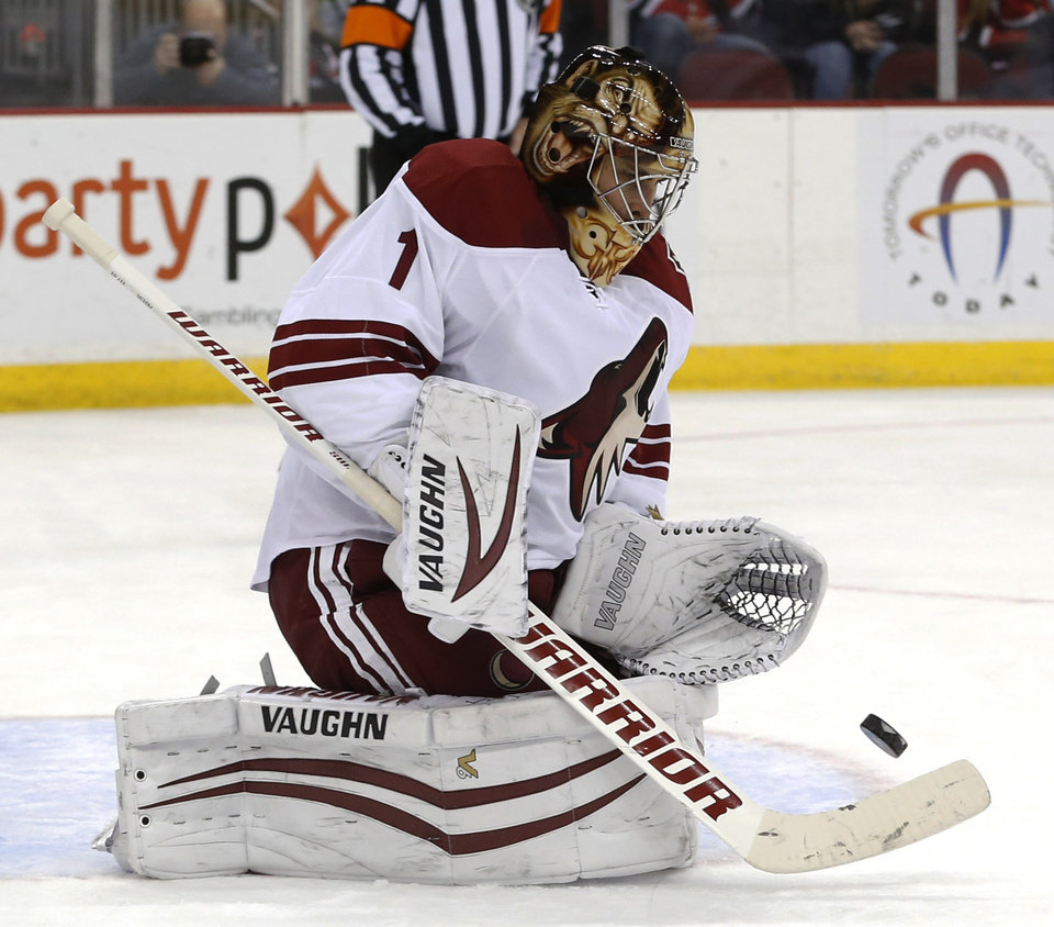Photo - Phoenix Coyotes goalie Thomas Greiss, of Germany, makes a save on a shot by the New Jersey Devils during the second period of an NHL hockey game, Thursday, March 27, 2014, in Newark, N.J. (AP Photo/Julio Cortez)