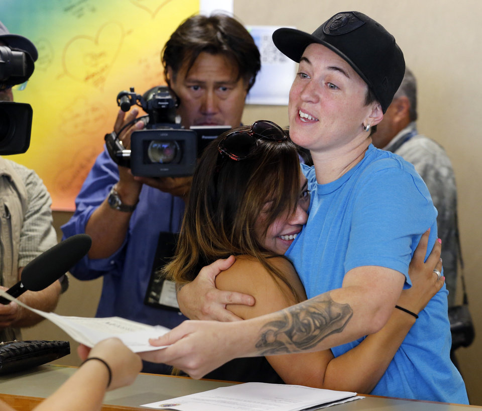 Photo - Samantha Getman, right, and Victoria Quintana embrace as they receive their marriage license at the Denver Clerk's office on Thursday, July 10, 2014. They were the first couple to receive a marriage licence in Denver, after clerk Debra Johnson began issuing licenses to same sex couples on Thursday. (AP Photo/Ed Andrieski)