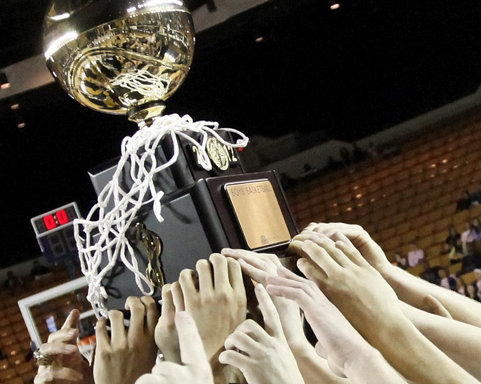 Bishop McGuinness celebrates with the gold ball championship trophy after the Class 5A boys high school basketball state tournament championship game between Bishop McGuinness and East Central at the Mabee Center in Tulsa, Okla., Saturday, March 10, 2012. McGuinness won, 54-41. Photo by Nate Billings, The Oklahoman