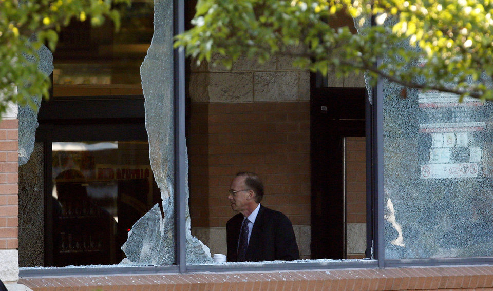 Photo -   Middlesex County prosecutor Bruce Kaplan is seen through two broken windows as he arrives at the scene of a shooting at a Pathmark grocery store in Old Bridge, N.J., Friday, Aug. 31, 2012. At least three people have died in the shooting. A law enforcement official briefed on the shooting says the person believed to be the shooter is among the dead. (AP Photo/Julio Cortez)