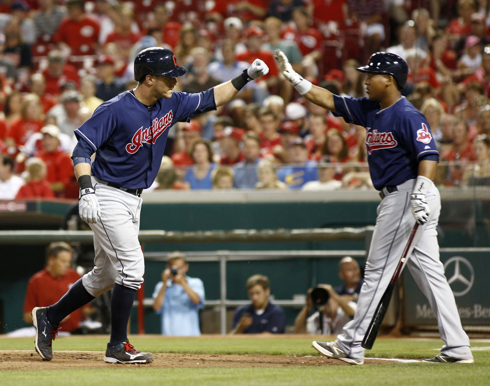 Photo - Cleveland Indians' Yan Gomes, left, is congratulated by Jose Ramirez, right, after Gomes hit a solo home run off Cincinnati Reds starting pitcher Mat Latos in the eighth inning of a baseball game, Wednesday, Aug. 6, 2014, in Cincinnati. The Reds won 8-3. (AP Photo/David Kohl)