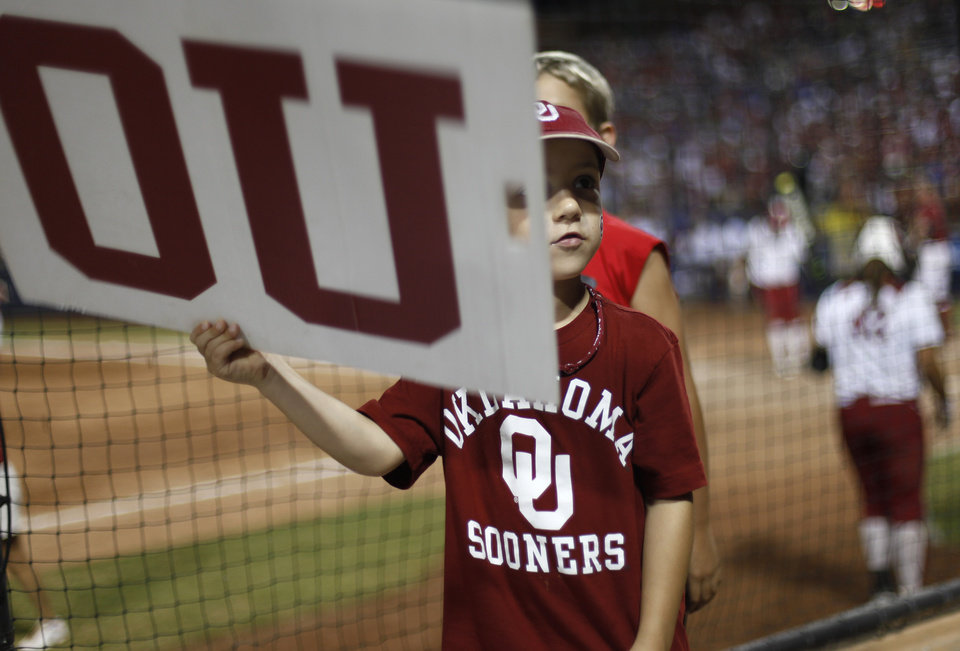 Photo - Jack Mackay, 7, of Norman, leads the crowd in cheer during a Women's College World Series softball game between OU and Alabama at ASA Hall of Fame Stadium in Oklahoma City, Tuesday, June 5, 2012.  Photo by Garett Fisbeck, The Oklahoman