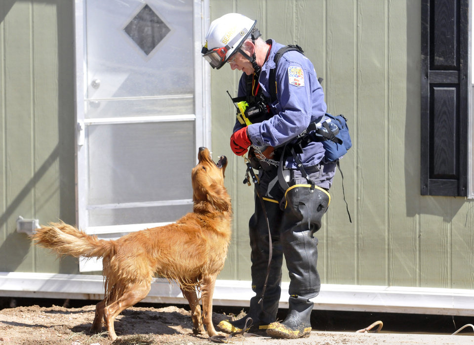 Photo - A search and rescue K-9 unit checks a few homes during FEMA's sweep through the area Sept. 18, 2013 in Evans, Colo. (AP Photo/The Greeley Tribune, Joshua Polson)