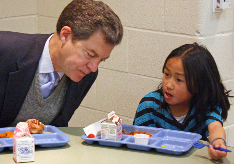 FILE - In this Jan. 23, 2014 file photo Kansas Gov. Sam Brownback, left, leans in to listen to Xen Hesse as the two each lunch at Roesland Elementary School in Roeland Park, Kan. On Friday, March 7, 2014, the Kansas Supreme Court said the state\'s current public school funding levels are unconstitutional. The case has broader implications beyond the classroom: Kansas enacted sweeping cuts to income taxes championed by Brownback that have reduced the amount of available resources to comply with a court order. (AP Photo/John Milburn, File)