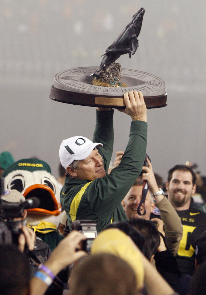 Photo - Oregon head coach Mike Bellotti raises the championship trophy after the Holiday Bowl college football game between Oklahoma State and Oregon at Qualcomm Stadium in San Diego, Tuesday, Dec. 30, 2008. Oregon won, 42-31. PHOTO BY NATE BILLINGS, THE OKLAHOMAN