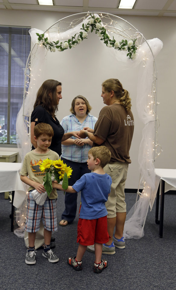 Photo - Melody Merida, center, marries Erin Lynae Fox, right, and Jennifer Elizabeth Fox as their sons Isaac, 7, left, and Redmond, 4, look on in the marion County Clerks office in Indianapolis, Wednesday, June 25, 2014. A federal judge struck down Indiana's ban on same-sex marriage Wednesday in a ruling that immediately allowed gay couples to wed. (AP Photo/Michael Conroy)