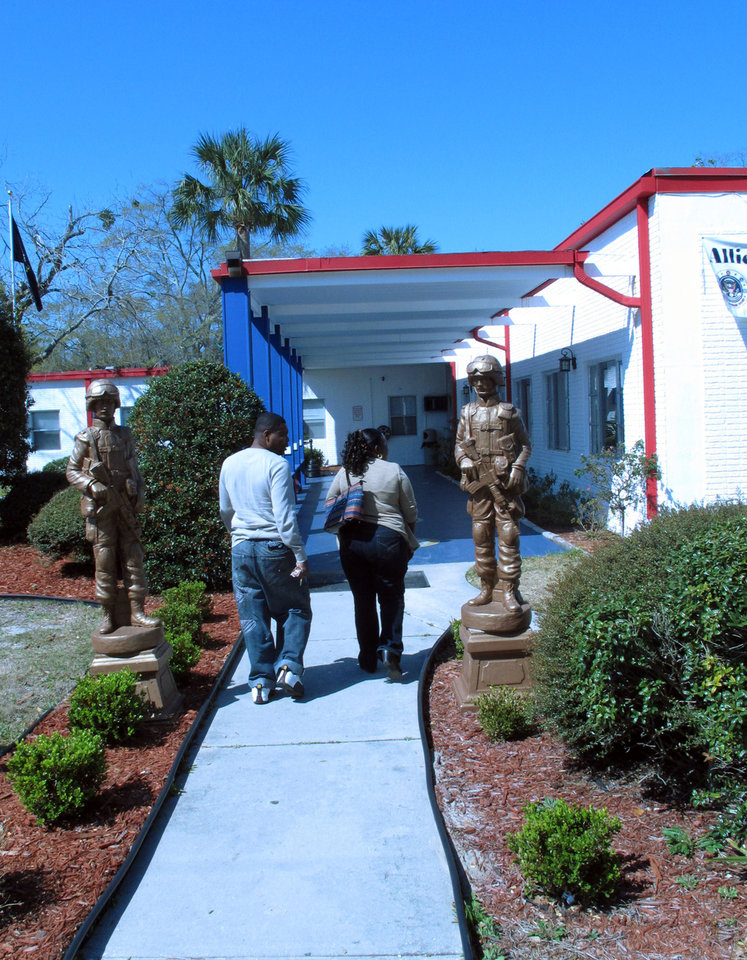 Photo - A couple walks past statues of soldiers at the entance to the Allied Veterans Center in Jacksonville, Fla., on Thursday, March 14, 2013. Center officials say they may have to close by the end of June because of a lack of funding. They have relied on money from Allied Veterans of the World, a group that's had its leaders arrested and assets seized as part of an investigation into illegal gambling in Florida. (AP Photo/Russ Bynum)