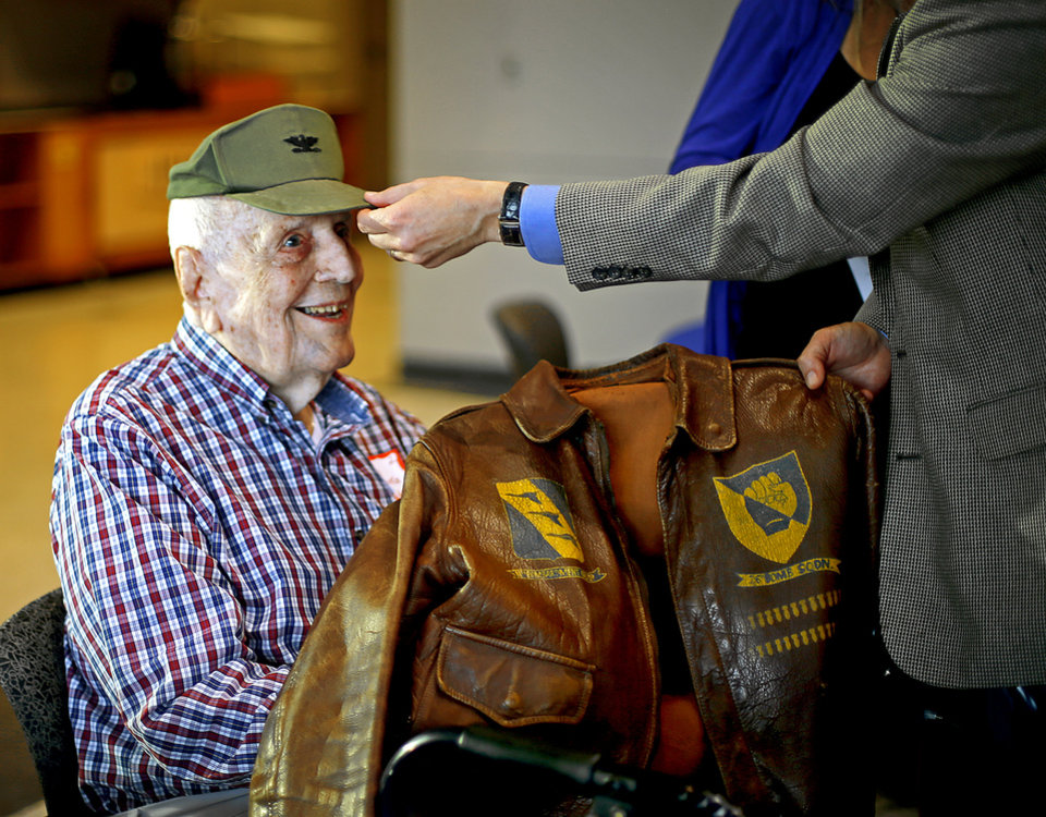 Photo - Retired Col. John R. Burks sits while his son-in-law Mike Anderson gives Burks his hat from Vietnam and his WWII flight jacket before the start of an Oklahoma Honor Flight send-off ceremony at Rose State College in Midwest City, Okla., Tuesday, October 7, 2014. Photo by Bryan Terry, The Oklahoman