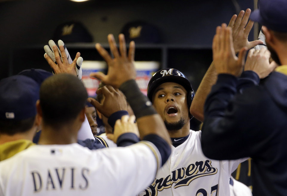Photo - Milwaukee Brewers' Carlos Gomez is congratulated in the dugout after hitting a home run during the first inning of a baseball game against the Arizona Diamondbacks Monday, May 5, 2014, in Milwaukee. (AP Photo/Morry Gash)