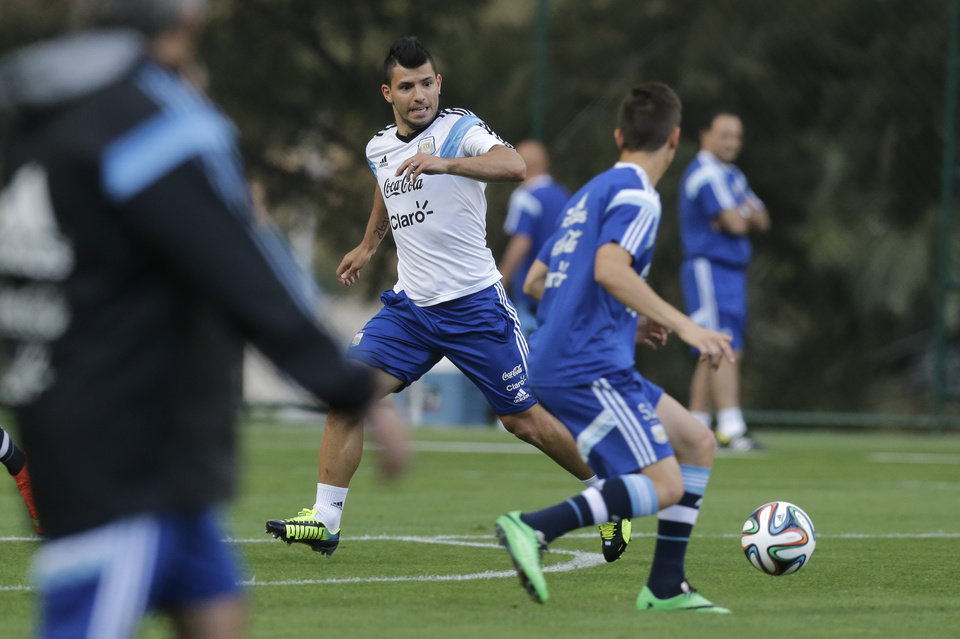 Photo - Argentina's Sergio Aguero, center, runs for the ball during a training session in Vespesiano, near Belo Horizonte, Brazil, Thursday, July 10, 2014. On Sunday, Argentina faces Germany for the World Cup final soccer match in Rio de Janeiro. (AP Photo/Victor R. Caivano)